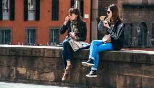 Turystki jedzą lody na zbytkowym moście we Florencji