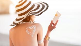 Kobieta nakłada krem przeciwsłoneczny