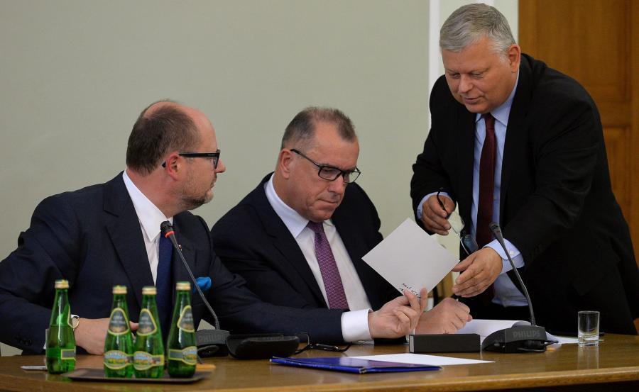 Adamowicz, jego prawnik i poseł Suski oglądają zdjęcie