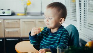 Chłopiec je cytrynę