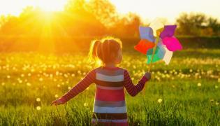 Dziecko spaceruje w słońcu po łące