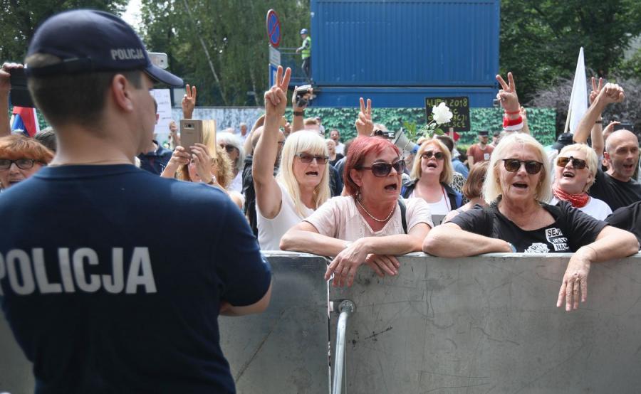 Policjant i demonstracja przeciwników reformy sądownictwa przed Sejmem