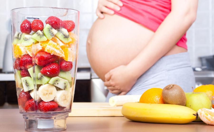 Kobieta w ciąży przygotowuje koktajl owocowy