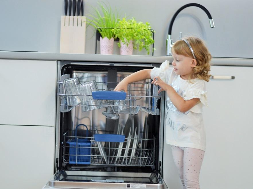 Dziewczynka rozpakowuje zmywarkę