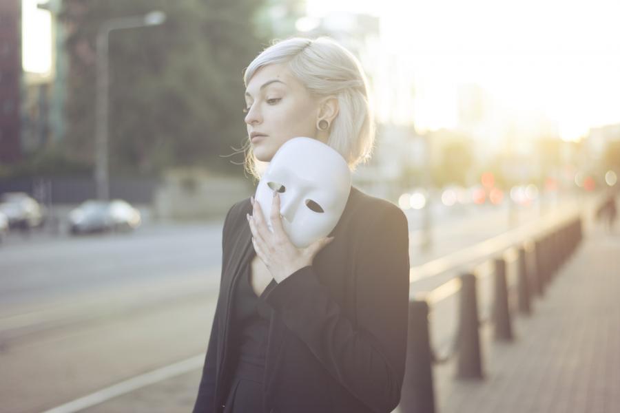 Kobieta trzyma w ręku maskę