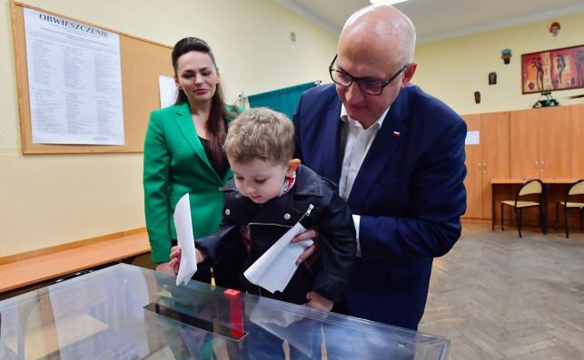 Minister spraw wewnętrznych i administracji Joachim Brudziński (P) z żoną Arlettą (L) i synem Ignacym głosują w lokalu wyborczym w Szczecinie