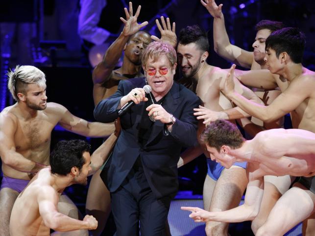 """Elton John śpiewający """"Like A Virgin"""" Madonny w towarzystwie półnagich tancerzy w nowojorskiej Carnegie Hall (13 maja 2010)"""