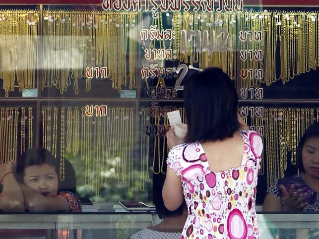 Ekspedientka sortuje złotą biżuterię w sklepie ze złotem, w Bangkoku w Tajlandii