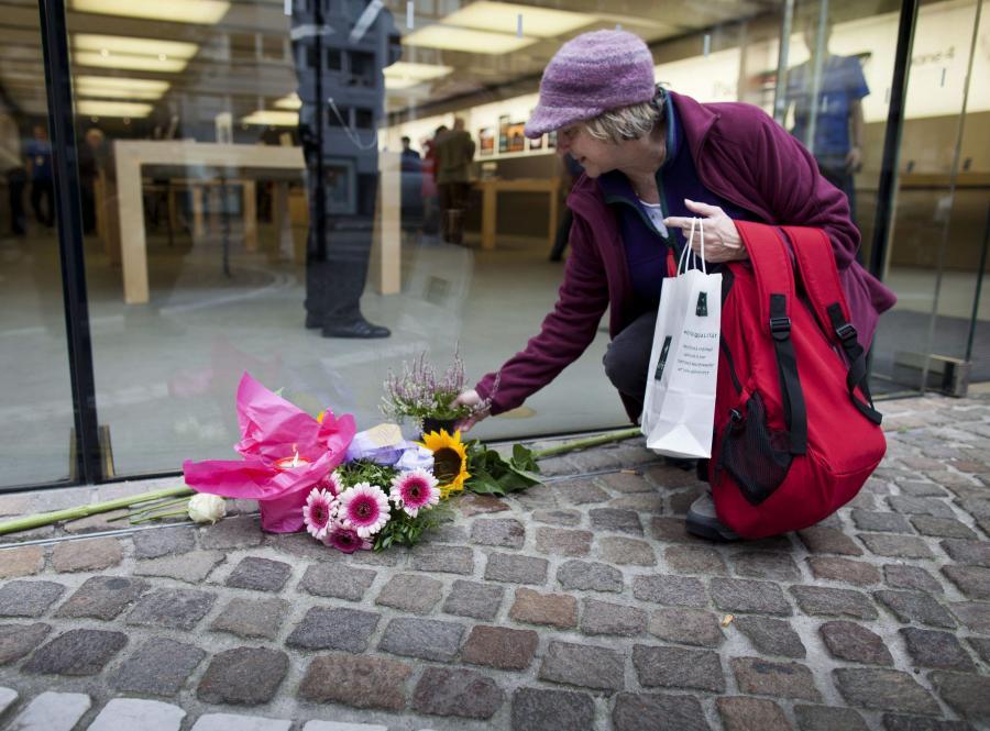 Tamara Holden z Kalifornii składa kwiaty pod sklepem Apple'a we Frankfurcie nad Menem