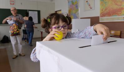 """Głosowanie w Obwodowej Komisji ds. Referendum nr 47. Mieszkańcy Krakowa uczestniczą 25 bm. w lokalnym referendum, w którym wypowiadają się czy chcą organizacji Zimowych Igrzysk Olimpijskich w Krakowie w 2022 roku. Dzieci """"pomagają"""" rodzicom we wrzuceniu karty do głosowania do urny"""