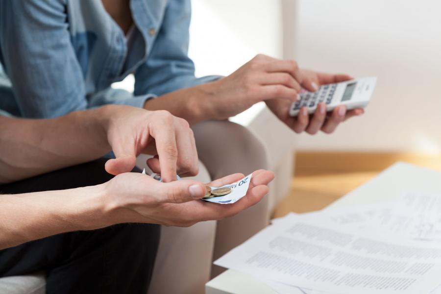 Mężczyzna i kobieta z kalkulatorem w ręku przeliczają pieniądze