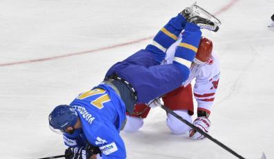Alexei Vorontsov (L) z Kazachstanu przelatuje nad Polakiem Grzegorzem Pasiutem (P) podczas meczu hokejowych mistrzostw świata dywizji 1A w Krakowie