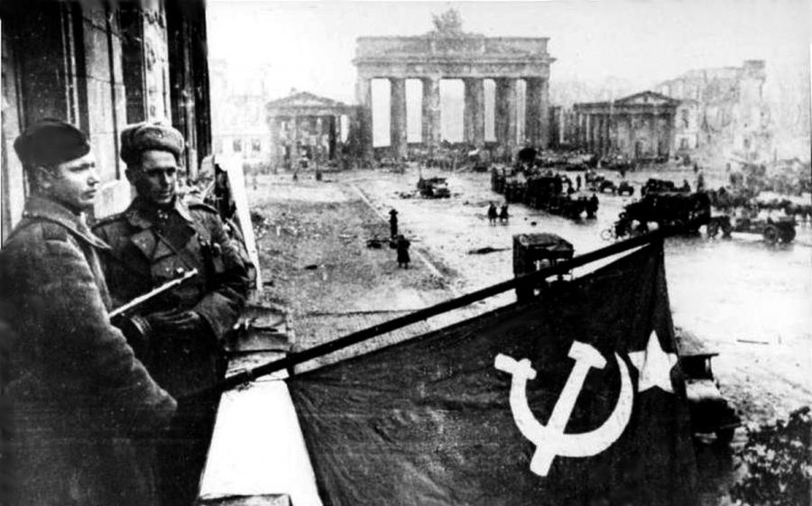 """Berlin 1945. Sowieccy żołnierze z flagą ZSRR w zdobytej stolicy III Rzeszy (fot. Bundesarchiv Bild 183-R77767, Berlin, Rotarmisten Unter den Linden"""" autorstwa Bundesarchiv, Bild 183-R77767 / CC-BY-SA)"""