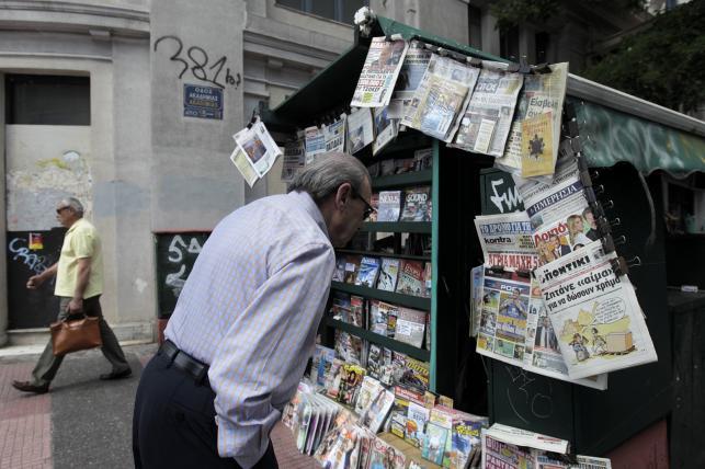Mężczyzna czyta nagłówki gazet w Atenach
