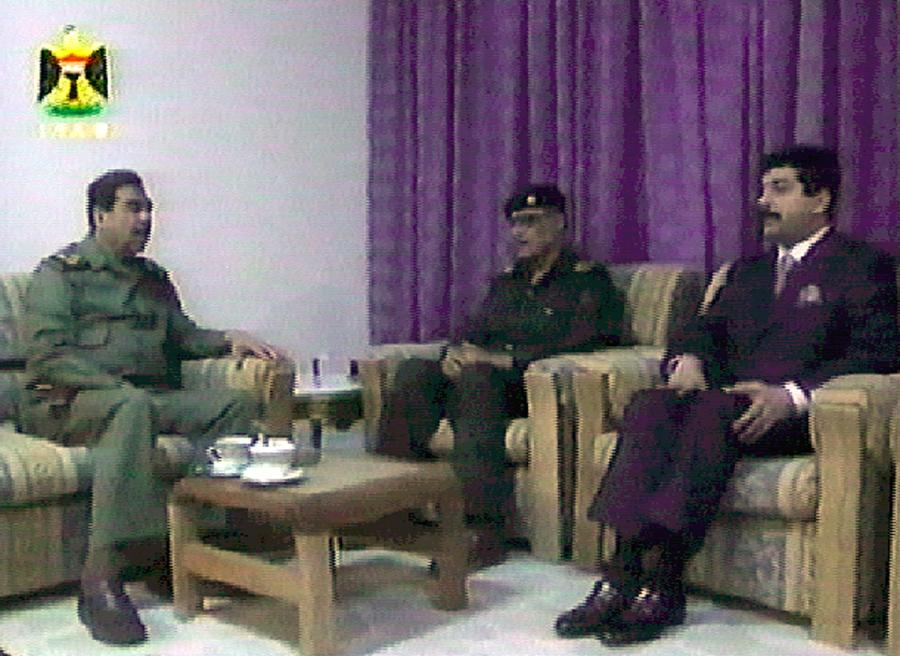 Zdjęcie z irackiej telewizji z 24 marca 2003 r. pokazujące prezydenta Iraku Saddama Husajna (L) i jego młodszego syna Kusaja (P), dowódcy Gwardii Republikańskiej na spotkaniu z Yahią al-Abbudi z partii Baas z rejonu Basry