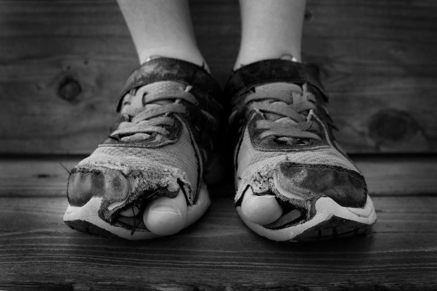 Stopy dziecka w dziurawych butach