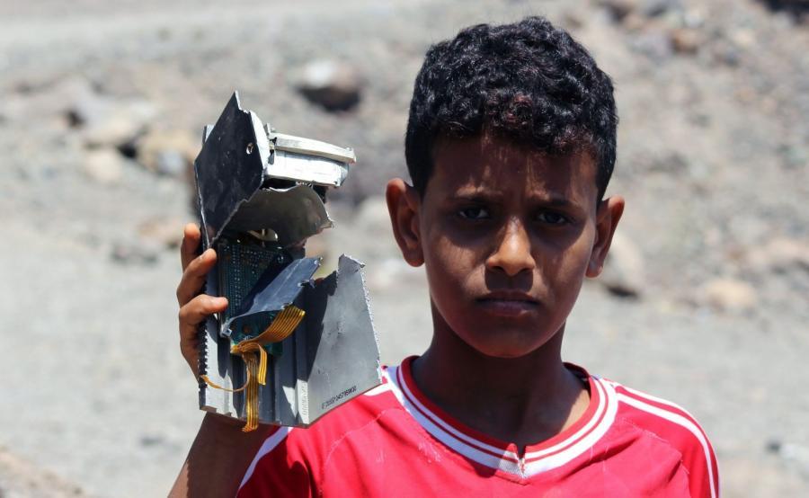Jemen. Chłopiec prezentuje kawałek rozbitego samolotu sił koalicji dowodzonej przez Arabię Saudyjską